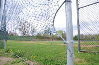 broke-and-bent-chain-links-on-chain-link-fence-at-baseball-field-backdrop