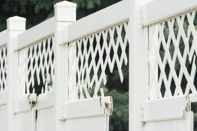 damaged-white-vinyl-fence-with-holes-on-the-top-lattice